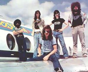 Boston with Tom Scholz (second from left) ... check out the  The perfectionist Scholz soon had his mates back in the studio to record a second album, but despite producing hit singles and going multi-platinum, there was always the feeling that Don t Look Back was a repeat performance of the first album. <br /><br />Fiercely independent, Scholz refused to allow himself to be pressured by Epic into rush-recording a third album. Instead, he formed a company called Scholz Research & Development to manufacture the signal-processing devices that he was designing for musical instruments. Through this company he became a multi-millionaire all over again, as his Rockman headphone amp and Power Soak monitors became state of the art! <br /><br />This wasn t thrilling to the record company, Boston s management and indeed some of Scholz s own band members. In fact it was then that legal troubles began to dog Scholz and Boston, as arguments over release schedules and royalties got out of control. Scholz spent most of the early 1980s extricating himself from this mess, and Goudreau and Delp recorded an album together. It wasn t until 1985 that Boston began recording its third album in earnest, and by this time Scholz and Delp were the only founder members left, although Masdea was recalled to replace Hashian. <br /><br />Defying those who maintain that lightning can t strike twice, Boston created yet another multi-platinum work with Third Stage. The chart-topping ballad Amanda became yet another instant evergreen, and while it was arguable that Boston was just churning out watered-down versions of the same album over and over again, there was clearly an audience of millions willing to lap up the stuff. <br /><br />And still the troubles persisted. Inter-band royalty clashes were now the order of the day, with Scholz being sued by not just Hashian but Masdea as well! <br />Still, it was hard for his band-mates to portray Scholz as the villain of the piece while the man actively pursued a variety of noble causes. Aside from anti-drug and pro-vegetarian campaigns, Scholz actually set up a foundation supporting animal rights and helping to 																																																																																																																																																																																																																																																																																																												<a href=